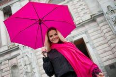 Schöne junge und glückliche blonde Frau mit buntem Regenschirm auf der Straße Das Konzept der Bestimmtheit und des Optimismus Lizenzfreie Stockbilder