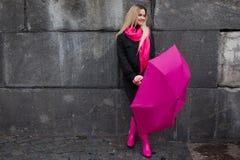 Schöne junge und glückliche blonde Frau mit buntem Regenschirm auf der Straße Das Konzept der Bestimmtheit und des Optimismus Lizenzfreies Stockbild