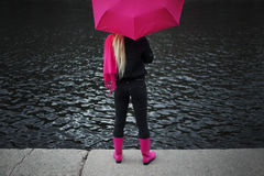 Schöne junge und glückliche blonde Frau mit buntem Regenschirm auf der Straße Das Konzept der Bestimmtheit und des Optimismus Stockfoto