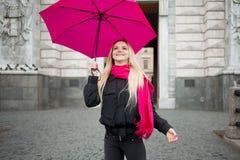 Schöne junge und glückliche blonde Frau mit buntem Regenschirm auf der Straße Das Konzept der Bestimmtheit und des Optimismus Lizenzfreie Stockfotografie