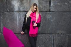 Schöne junge und glückliche blonde Frau mit buntem Regenschirm auf der Straße Das Konzept der Bestimmtheit und des Optimismus Stockfotos