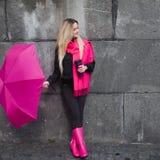 Schöne junge und glückliche blonde Frau mit buntem Regenschirm auf der Straße Das Konzept der Bestimmtheit und des Optimismus Stockbilder