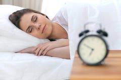 Schöne junge und glückliche schlafende Frau beim im Bett bequem liegen und himmlisch lächeln stockfoto