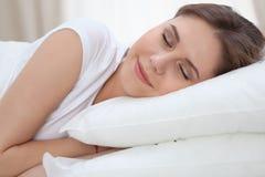 Schöne junge und glückliche schlafende Frau beim im Bett bequem liegen und himmlisch lächeln lizenzfreie stockfotografie