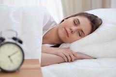 Schöne junge und glückliche schlafende Frau beim im Bett bequem liegen und himmlisch lächeln stockbilder