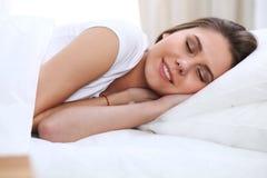 Schöne junge und glückliche schlafende Frau beim im Bett bequem liegen und himmlisch lächeln lizenzfreies stockbild