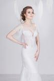 Schöne junge und träumerische Braut in einem luxuriösen Spitzehochzeitskleid Lizenzfreie Stockfotos
