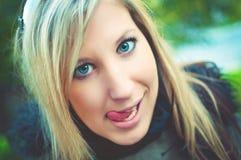 Schöne junge unverschämte Frau, die ihre Zunge zeigt lizenzfreie stockbilder