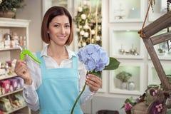 Schöne junge Verkäuferin arbeitet in der Blume Lizenzfreie Stockfotos