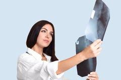 Schöne junge weibliche Krankenschwester oder Doktor überprüft Strahlen aufmerksam X vor und nach treatmnet, macht Diagnose, denkt stockfotografie