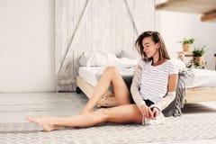Schöne junge weibliche sexy Frau, die im Schlafzimmer am faulen Wochenendenmorgen, tragende zufällige Mode sich entspannt stockbild