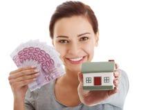 Schöne junge, zufällige Frau, die Geld und Haus hält. Lizenzfreie Stockfotos
