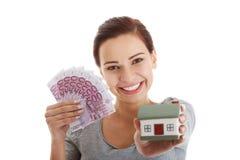 Schöne junge, zufällige Frau, die Geld und Haus hält. Stockbild