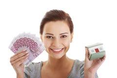 Schöne junge, zufällige Frau, die Geld und Haus hält. Stockfotos