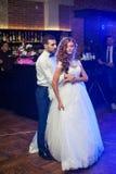 Schöne Jungvermähltenpaare tanzen zuerst an der Hochzeit Stockfotografie