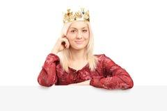 Schöne Königin mit einer Diamantkrone, die hinter Platte aufwirft stockbild