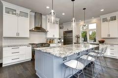 Schöne Küche im zeitgenössischen modernen Luxushauptinnenraum mit Insel- und Edelstahlstühlen stockbild