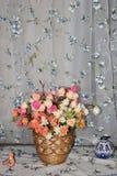 Schöne künstliche Rosen in einem Weidenkorb auf einem Stoffhintergrund lizenzfreies stockfoto