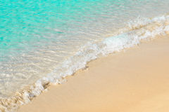Schöne Küste mit Gischt und Sand, transparentes blaues Meerwasser Stockfotos