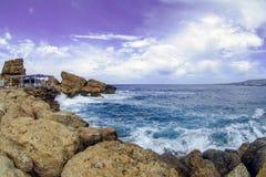 Schöne Küstenlinie mit den Wellen, die Felsen auf dem Strand schlagen stockfotografie