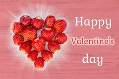 Schöne Karte mit einem Gruß am Valentinstag - Herzerdbeeren auf Beschaffenheiten und den Wörtern glücklicher Valentin eines rosa  stockfotos