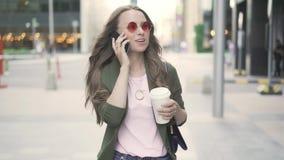 Schöne kaukasische Frau, die auf Smartphone in der Fallstadt geht und spricht stock video footage