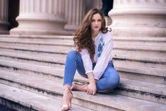 Schöne kaukasische Frau, die auf Treppe sitzt Stockfotografie