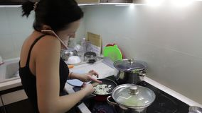 Schöne kaukasische Frau, die am Telefon beim Kochen spricht stock footage