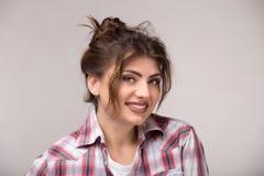 Schöne kaukasische Frau mit dem losen gelockten Haar lächelnd und Kamera betrachtend lizenzfreie stockbilder