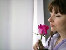 Schöne kaukasische Frau mit rosa Rose nahe dem Fenster lizenzfreie stockbilder