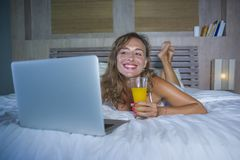 Schöne kaukasische Frau 30s, die auf Bett nachts im Hauptschlafzimmer unter Verwendung des Internets an der Laptop-Computer trink Stockbilder