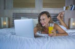 Schöne kaukasische Frau 30s, die auf Bett nachts im Hauptschlafzimmer unter Verwendung des Internets an der Laptop-Computer trink Lizenzfreies Stockfoto