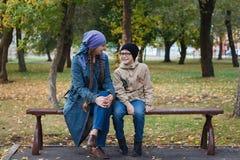 schöne kaukasische Frau und ihr Sohn, die im Park auf einer Bank, Herbst, Familie sitzt lizenzfreies stockfoto