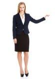 Schöne kaukasische Geschäftsfrau, die Hand auf leerem Raum hält. Lizenzfreies Stockbild