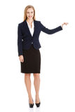 Schöne kaukasische Geschäftsfrau, die Hand auf leerem Raum hält. Stockfoto