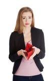 Schöne kaukasische Geschäftsfrau, die ihre leere rote Geldbörse überprüft stockfotografie