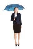 Schöne kaukasische Geschäftsfrau, die unter Regenschirm steht. stockfoto