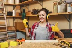 Schöne kaukasische junge Braunhaarfrau, die bei Tisch im Platz der Zimmereiwerkstatt arbeitet lizenzfreies stockbild