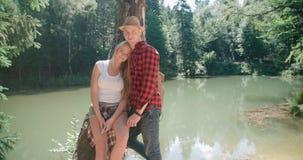 Schöne kaukasische Paare, die in einem Wald während des sonnigen Tages sich entspannen Lizenzfreie Stockbilder
