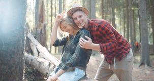 Schöne kaukasische Paare, die in einem Wald während des sonnigen Tages sich entspannen Stockfotografie