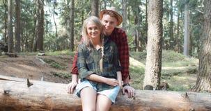 Schöne kaukasische Paare, die in einem Wald während des sonnigen Tages sich entspannen Lizenzfreies Stockbild