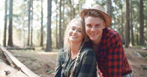 Schöne kaukasische Paare, die in einem Wald während des sonnigen Tages sich entspannen Lizenzfreies Stockfoto