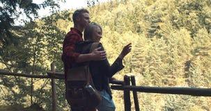 Schöne kaukasische Paare, die in einem Wald während des sonnigen Tages sich entspannen Stockfoto