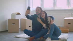 Schöne kaukasische Paare, die selfies unter Verwendung des Smartphone beim Sitzen auf dem Boden nahe Kartonkästen machen stock video footage