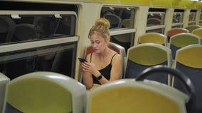 Schöne kaukasische weibliche touristische Fahrten in einem leeren Zug durch einen dunklen Tunnel Hinter den Sitzreihen sind Licht stock video footage