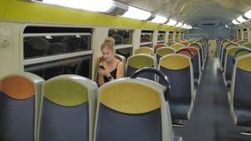 Schöne kaukasische weibliche touristische Fahrten in einem leeren zweistufigen Zug durch einen dunklen Tunnel Hinter den leeren R stock video footage