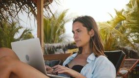 Schöne kaukasische Workaholic CEO-Geschäftsfraufunktion, im Urlaub schreibend im beweglichen Büro des Laptops im Strandstuhl stock video