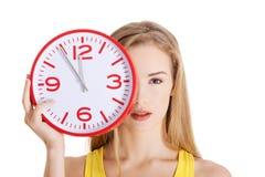 Schöne kaukasische zufällige Frau, die rote Uhr hält Lizenzfreies Stockfoto