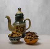 Schöne keramische Teekanne in der orientalischen Art und eine Schüssel Rosinen und Nüsse Lizenzfreie Stockfotos