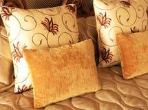 Schöne Kissen auf Bett Stockfotografie